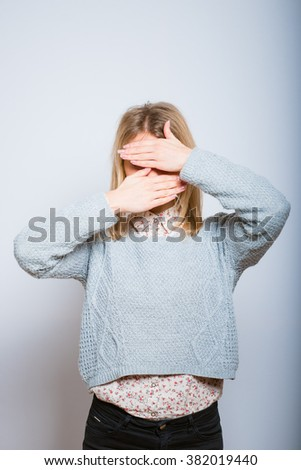 blond woman hides her face, isolated on a gray background