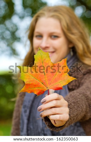 Blond woman holding a autumn leaf