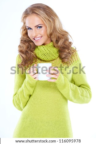 Blond woman holding cup of hot drink while she is isolated - stock photo