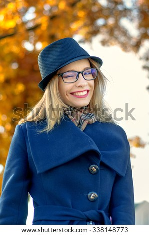 Blond woman in a blue hat and glasses on the background of yellow foliage