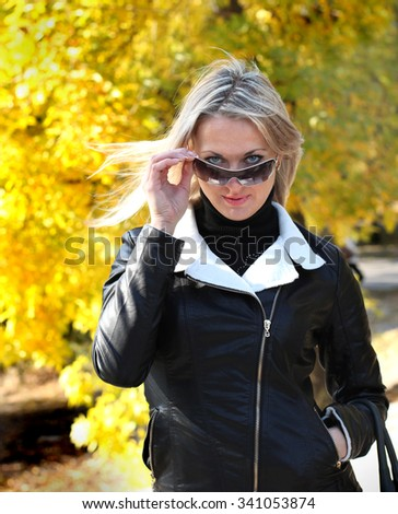 blond woman in black leather jacket on a yellow background  - stock photo