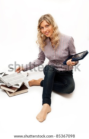 Blond woman in checked shirt with tablet pc and books - stock photo