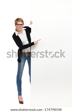 Blond woman in glasses holding banner and pointing at copy space. Full length studio shot isolated on white.