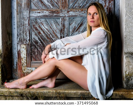 Blond woman in night dress sitting in front of an weathered door