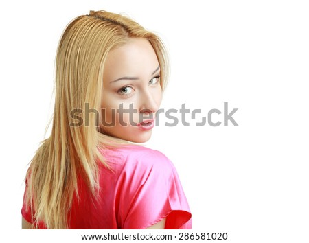 blond woman in pink shirt looking over her shoulder - stock photo