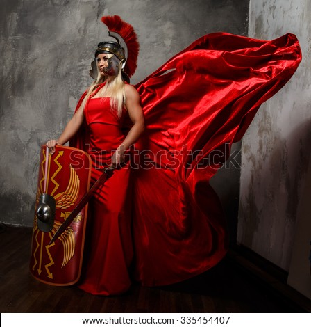 Blond woman in Roman red fluttering dress holds sword and shield.