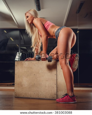 Blond woman in sexy denim shorts standing on a knee and holding one dumbbell.