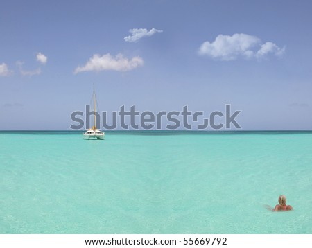 blond woman in the sea with a catamaran