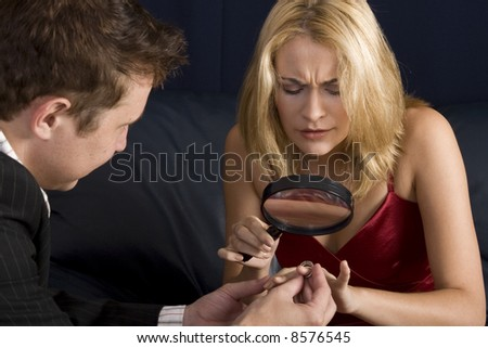Blond woman inspecting diamond size with magnifying glass prior to accepting proposal - stock photo