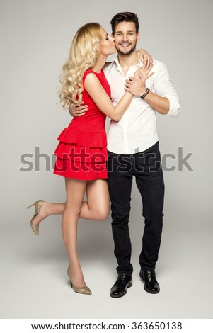 Blond woman kissing young man - stock photo