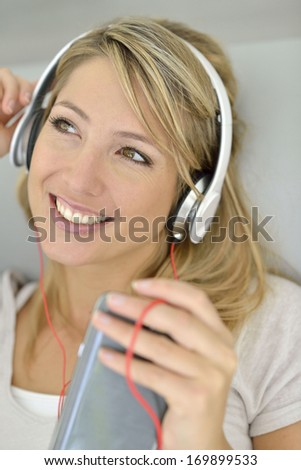 Blond woman listening to music with smartphone