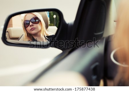Blond woman looking in the car mirror - stock photo
