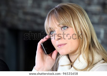Blond woman making telephone call from home - stock photo