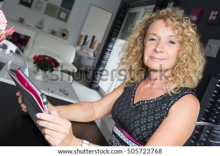 Blond woman mature sitting at home while using ebook reader.
