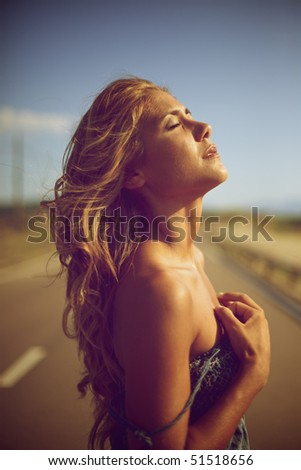 Blond woman on a sunset - stock photo