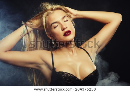 blond woman posing in lingerie over dark background