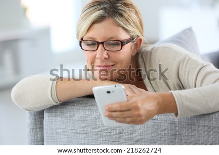 Blond woman reading text message on smartphone - stock photo