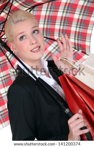 Blond woman shopping under the rain. - stock photo