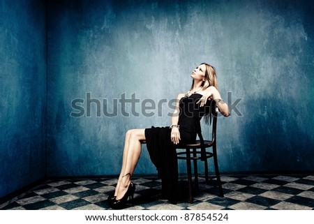 blond woman sit in empty room in elegant black dress and high heels