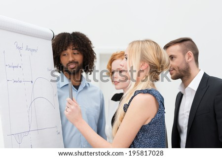 Blond woman standing with business colleagues in front of a flip chart drawing an analytical graph - stock photo