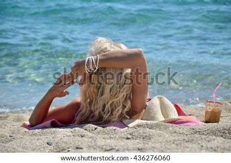 Blond woman sunbathing on beach, enjoying cold coffee frappe and looking at sea