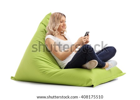 Blond woman texting on her cell phone seated on a green beanbag isolated on white background