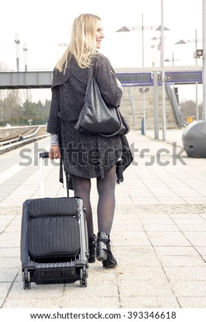 blond woman walking at train station with her suitcase - stock photo
