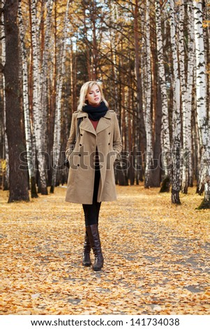 Blond woman walking in autumn forest - stock photo