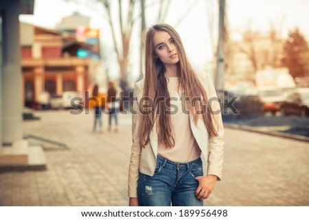 Blond woman walking on the city street - stock photo