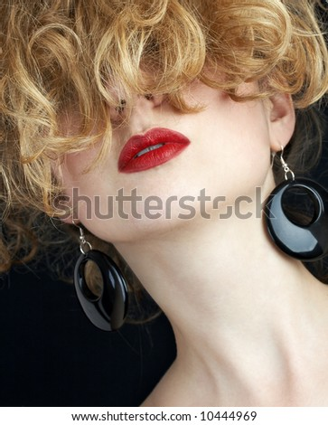 blond woman wearing fashionable black earrings and red lipstick - stock photo