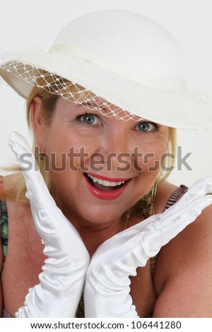 Blond woman wearing white hat with white gloves framing her face - stock photo