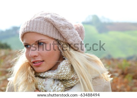 Blond woman wearing wool cap in autumn - stock photo