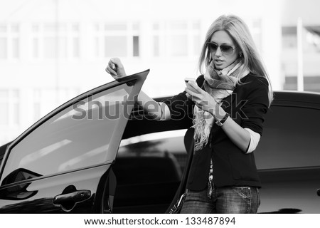 Blond woman with a car looking at mobile phone - stock photo