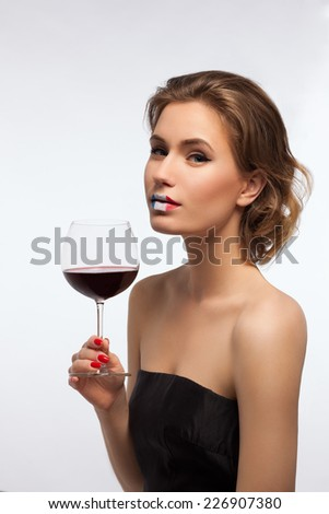 Blond woman with a glass of wine and French lips make-up on white background. - stock photo