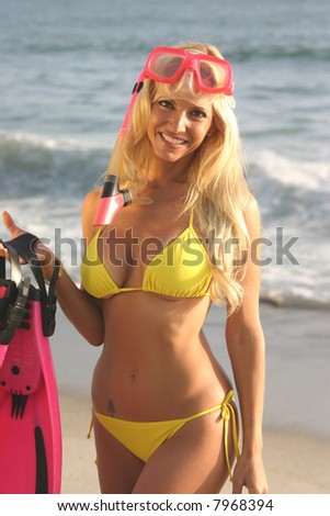 Blond woman with a snorkel,mask and fins on the beach. at Sunset