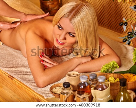 Blond woman with beautiful long hair getting massage in tropical spa. Visible hand masseuse.