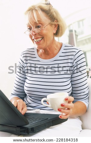 Blond woman with glasses laughing - stock photo