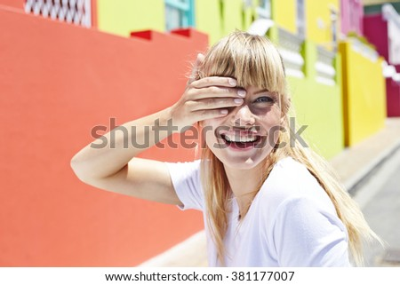 Blond woman with hand over eye, portrait