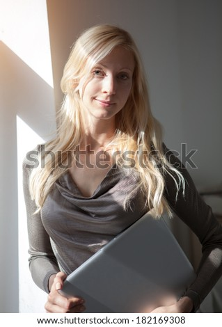 Blond woman with laptop near window - stock photo
