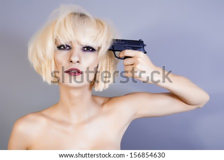 blond woman with pistol pointing on her head - stock photo