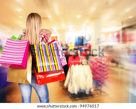 Blond woman with shopping bags in shopping center - stock photo