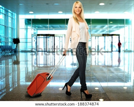 Blond woman with suitcase in airport  - stock photo