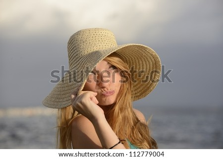 blond woman with sunhat on the beach posing - stock photo