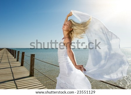 Blond woman with white shawl relaxing near the sea - stock photo