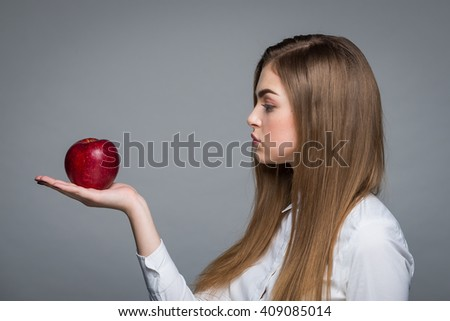 blond women in white blouse holding hand red apple, fashion portrait