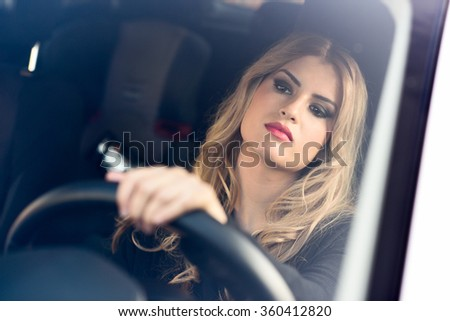 Blond young girl driving a sport car looking at the road - stock photo