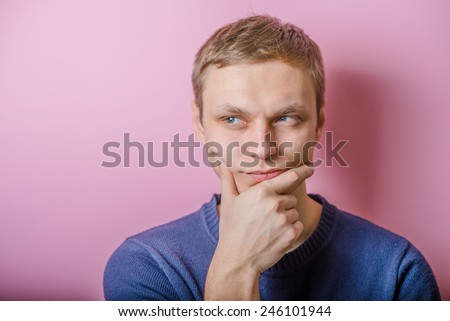 Blond young man thinks thinks. head resting on her hand, looking into the camera. Gesture.  - stock photo