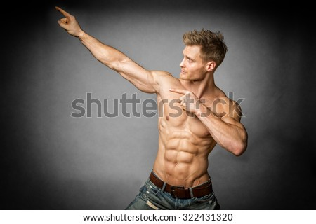 Blond young man with well trained body, abs and pecs and wearing a denim trousers look to the left - stock photo