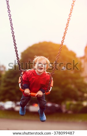 Blond young toddler boy swinging at children playground. Happy child having good time outdoors.