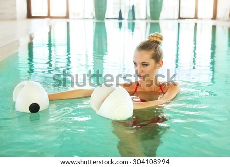 Blond young woman doing aqua aerobics with foam dumbbells in swimming pool at the leisure centre - stock photo
